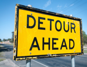 A sign warning of a detour on the road ahead, due to roadworks.